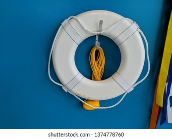 Water Safety White Life Preserver Flotation Ring Lifesaver Donut for the Pool with a Yellow Rope Hanging on a Metal Hook on a Blue Wall For Swimming and Lifeguards