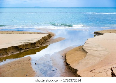 Water and sand on the shoreline in Follonica, Italy in winter in a cloudy day