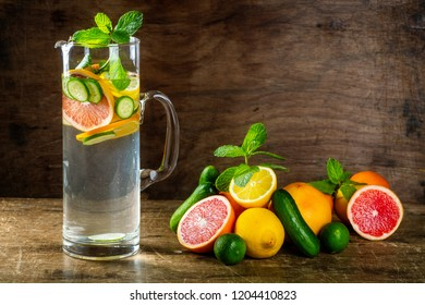 Water Sassy with lemon, grapefruit, orange, mint, cucumber and ginger, selective focus, on wooden background