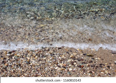 Water sea ocean sand pebbles beach swash wave waterline shallow surface texture clear summer nobody abstract background