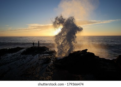 Water is shot up and out of a blowhole in the rocks in front of the early morning sunrise