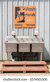 Water Sink and Sign telling people to wash their hands after visiting animals in the farm.