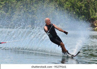 A water skier in his 60's preforming water skiing sport on a lake.