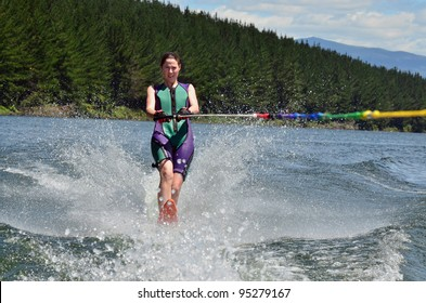 A water skier woman water skiing on a lake.