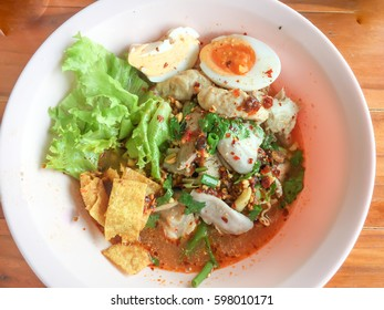 Water spicy noodles mixed with pork, wonton, livers and eggs in top view in Thailand style