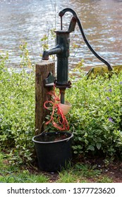 water spigot in the garden with water bucket cast iron well pump hand operated