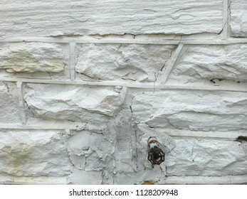 Water spigot on an old painted stone wall. Hole in wall was I filled with mortar and painted white. Rust and stains are visible