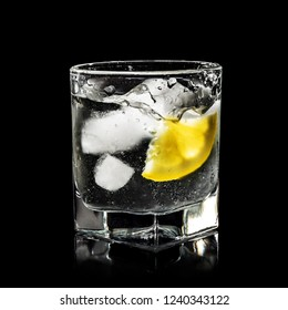 water splash in glass for alcohol with pure ice and yellow lemon isolated over black background