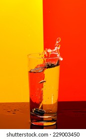 Water splash in glass on colorful background