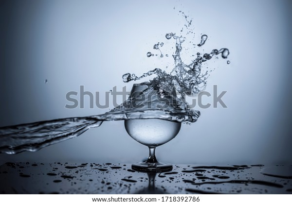 Water splash pattern on wine glass side high speed photography with radial gradient light background