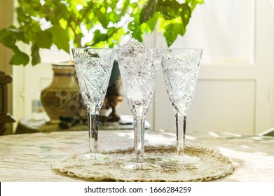 Water splash in wine glass. Three champagne glass on table in home interior. Pure still water for drink