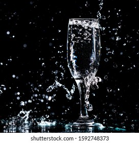Water with splashes in a glass on a black background.