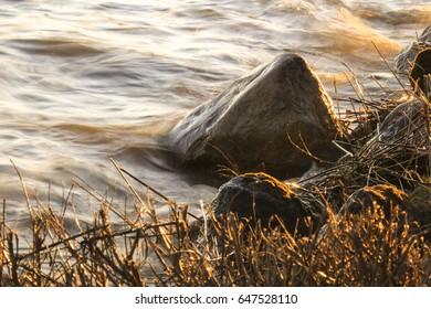 water splashes at rocky shore, golden sunlight
