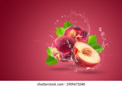 Water splashing on Ripe fresh Nectarine fruit isolated over red background.