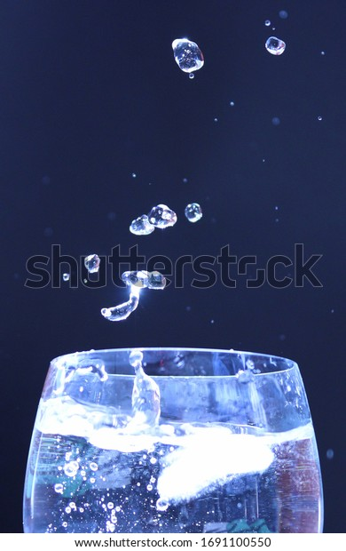 Water splashing out of a glass as an ice cube is dropped in to the water with droplets spraying in to the air on a black background.