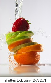 water splashing over sliced fruits