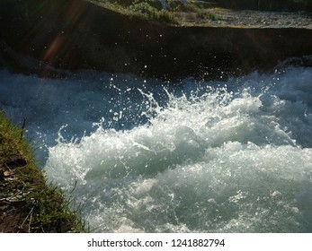 Water splashing and squirting after Ticinazzo sluice waterfall lightened by sun, surrounded by cotto bricks in Ticino river reserve in Galliate, Italy