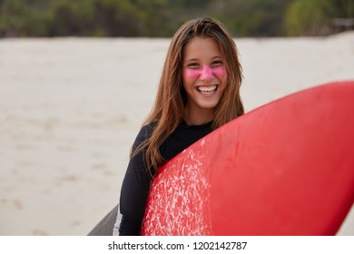 Water sport concept. Happy delighted surfboarder in diving suit, uses red board for hiting waves, being in good mood, poses against blurred background outdoor. Tourist during holiday in exotic country