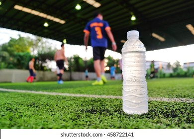 Water sport drink against blurred soccer background on green artificial grass
