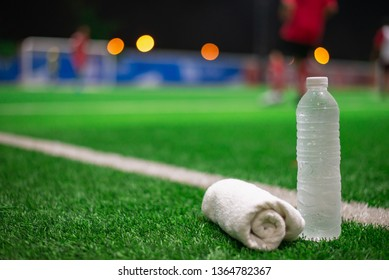 Water sport drink with towel blurred soccer background on green artificial grass at night.
