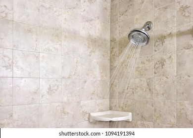 Water spraying from a water saving, conservation, shower head, in a modern tiled shower.