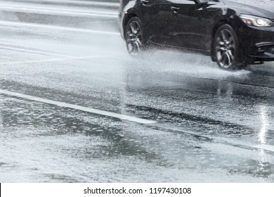water spraying from wheels of a car moving on wet city asphalt road
