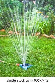 Water sprinkler. Irrigation system - technique of watering in the garden. Lawn sprinkler spraying water over green grass.