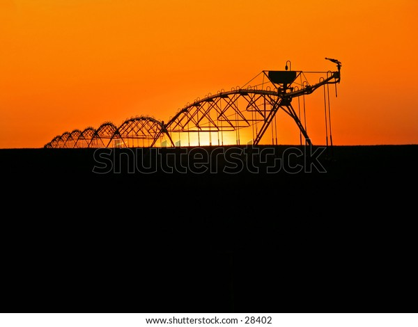 Water sprinklers silhouetted in prarie lands, sunset in background.