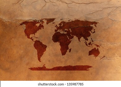 Water stain mark in the shape of a world map on an old vintage brown leather parchment.