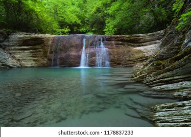 Water stream in mountain of Caucasus. Summer landscape with waterfall and water stream in forest of Caucasus mountain.