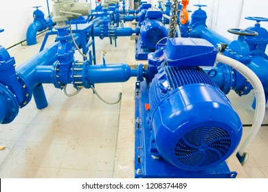Water supply and transfer system. blue pumps and pipes indoors