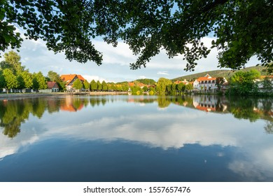 The water surface of the pond reflects the houses and the sky. Town of Ilsenburg in the Harz mountains
