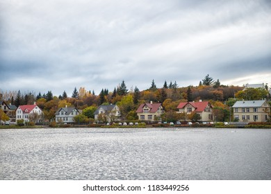 Water surface pond scandinavian city. Pond or lake nature environment destination. Pond surrounded numerous coloured old houses. Tjornin pond great place popular destination for families Reykjavik.