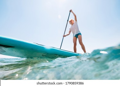 Water surface-level view angle to the smiling blonde teenager boy rowing stand up paddle board. Active family summer vacation time near the sea concept image.