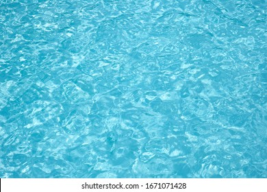 Water in swimming pool and rippled water detail for background. Light soft blue of swimming pool rippled water on texture reflection