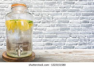 Water tank or lemonade dispenser isolated on grey bricks wall