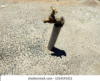 water tap attached to a slub of concrete in a dry hot sunny day