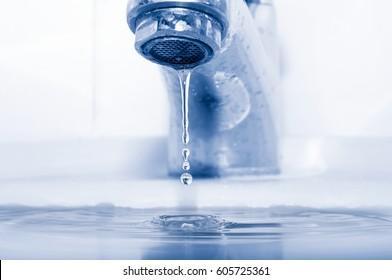 Water tap and falling drops closeup