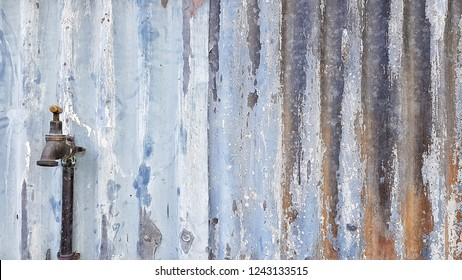 Water tap on old rusty zinc wall. Zinc texture background.  Metal Abstract background.