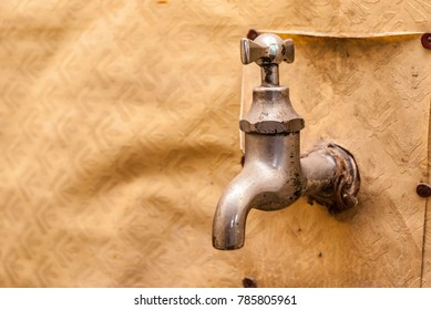 Water tap on a wall covered with a wallpaper.