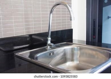Water tap with sink in modern kitchen.