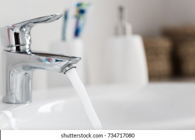 Water tap with turned n water in modern bathroom. Horizontal crop with shallow depth of field