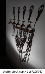 Water taps, chains, shadows from these chains on the wall