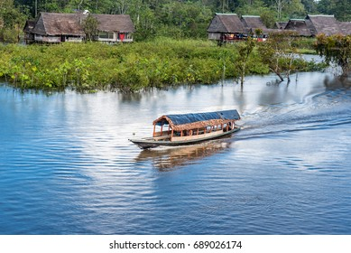 Water taxi on the Rio Yarapa Amazon river with small village in the background