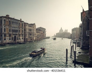 Water taxis and ferries on the grand canal on a misty early morning looking towards the Basilica di Santa Maria della Salute