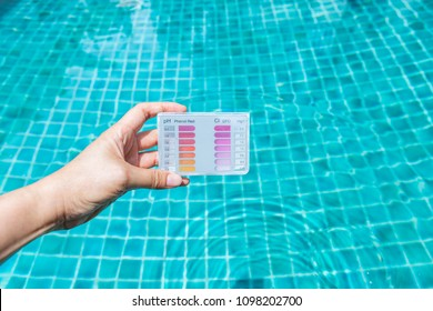 Water testing test kit in girl hand dipping in clear swimming pool water