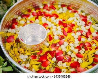 Water with thai perfume in water dipper with colorful flowers petal and garland for Songkran festival, Thailand, Bowl with flowers such as jasmine, rose for bathing Buddha statue On Songkran Day