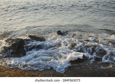 Water topped with foam comes to rest as the beach is reached past the last rocks at low tide.