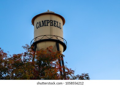 Water Tower against a blue sky with Fall leaves. City of Campbell, Northern California.