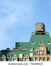 Water tower on the rooftop of a New York City building with a distinctive green roof, against a blue sky